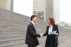 Male lawyer speaking with female client. Layer and client standing on big gray stairs. Woman hold documents about court statement in hand. Man tell about very stock photography