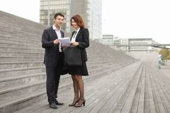 Male lawyer speaking with female client. Layer and client standing on big gray stairs. Woman hold documents about court statement in hand. Man tell about very royalty free stock images