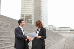Male lawyer speaking with female client. Layer and client standing on big gray stairs. Woman hold documents about court statement in hand. Man tell about very stock photo