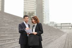 Male lawyer speaking with female client. Layer and client standing on big gray stairs. Woman hold documents about court statement in hand. Man tell about very royalty free stock image