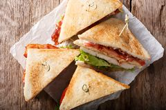Layer club sandwich with turkey meat, bacon, tomatoes and lettuce macro. Horizontal top view. Layer club sandwich with turkey meat, bacon, tomatoes and lettuce stock photo