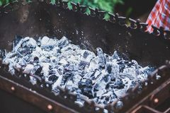 Hot coals in metal brazier closeup. Layer of hot coals in a rectangular forged brazier closeup Royalty Free Stock Photos