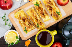 Layer pie with apples and cinnamon on a cutting board, cup of tea Stock Image