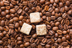 Layer of roasted coffee beans with three sugar cubes Royalty Free Stock Photography