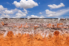 Layer of soil beneath the asphalt road with blue sky Stock Images