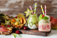 Layered berry and chia seeds smoothies and exotic fruit salad. In pineapple half Stock Photography