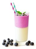 Layered blueberry and coconut smoothie with scattered berries over white Stock Images