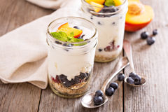 Layered breakfast parfait with granola and fruits. Layered breakfast parfait with granola, peaches and berries Stock Photography