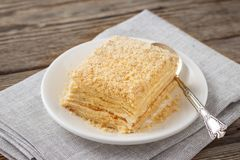 Layered cake with cream Napoleon millefeuille vanilla slice. On a white plate stock photos