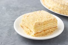 Layered cake with cream Napoleon millefeuille vanilla slice on a white plate.  stock photo