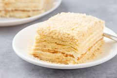 Layered cake with cream Napoleon millefeuille vanilla slice on a white plate.  stock photography