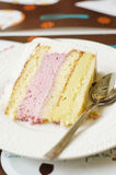 Layered cake with pistachio and raspberry cream. Teaspoon on plate Stock Photo