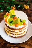 Layered cake with vanilla mascarpone cream cheese, lemon curd or lemon custard decorated with fresh grape, lemon, winter cherry an royalty free stock image