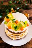 Layered cake with vanilla mascarpone cream cheese, lemon curd or lemon custard decorated with fresh grape, lemon, winter cherry an. D mint on a plate on a wooden royalty free stock photo