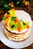 Layered cake with vanilla mascarpone cream cheese, lemon curd or lemon custard decorated with fresh grape, lemon, winter cherry an royalty free stock photo