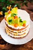 Layered cake with vanilla mascarpone cream cheese, lemon curd or lemon custard decorated with fresh grape, lemon, winter cherry an. D mint on a plate on a wooden royalty free stock photos