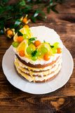 Layered cake with vanilla mascarpone cream cheese, lemon curd or lemon custard decorated with fresh grape, lemon, winter cherry an. D mint on a plate on a wooden stock image