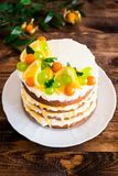 Layered cake with vanilla mascarpone cream cheese, lemon curd or lemon custard decorated with fresh grape, lemon, winter cherry an. D mint on a plate on a wooden stock photography