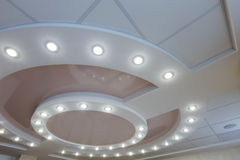 Layered ceiling with embedded lights and stretched ceiling inlay. Modern layered ceiling with embedded lights and stretched ceiling inlay, light turned on stock photo