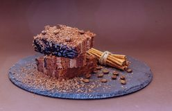 Layered chocolate cake with coffee beans and cinnamon. Dark background Stock Photo