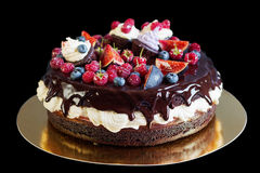 Layered chocolate cake with fruit. Isolated on black. Layered chocolate cake decorated with cream and fruit. Isolated on black background Royalty Free Stock Images