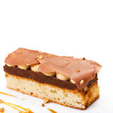Layered dessert with caramel, nuts and chocolate on white plate, Stock Images
