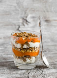 Layered dessert with cottage cheese, papaya puree and homemade granola served in a glass. Royalty Free Stock Photos