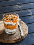 Layered dessert with cream cheese, papaya puree and homemade granola. Royalty Free Stock Images