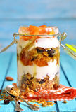 Layered dessert from granola,yogurt,persimmon and honey. Stock Photos