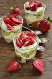 Layered dessert with strawberries, kiwi, biscuit and cream Royalty Free Stock Images