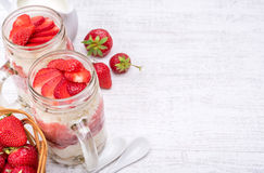 Layered dessert with strawberry and cream cheese in glass jar. Stock Photos