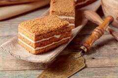 Layered honey cake with cream. On a old wooden table stock photo