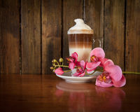 Layered Latte with Orchid. Layered Latte on saucer with orchid. Sat on wooden table against wooden background Royalty Free Stock Photo