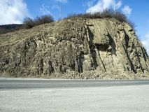 Layered rocks on the slopes of the Georgian military road stock image