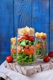 Layered salad with cheese, kale, carrot, chicken, cucumbers and cherry tomatoes. In glass mason jars royalty free stock photo