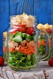 Layered salad with cheese, kale, carrot, chicken, cucumbers and cherry tomatoes. In glass mason jars stock photos