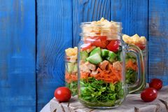 Layered salad with cheese, kale, carrot, chicken, cucumbers and cherry tomatoes. In glass mason jars stock images