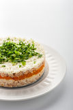 Layered salad with eggs and fish on the white ceramic plate vertical Royalty Free Stock Photography