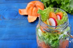 Layered salad in a jar with mandarins, radish, lettuce leaves, carrot and dressing. Against the blue background royalty free stock photos