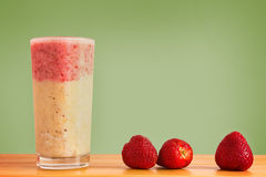 Layered Smoothie with Strawberries and Bananas. Strawberries and Banana Smoothie with a Green Background Royalty Free Stock Photos