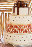 Layered white wedding cake with chocolate detail. On silver serving dish stock photo