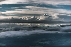 Layers of clouds in the evening sky above rolling hills landscap Stock Photos