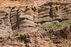 LAYERS OF MOLDED ROCK. Molded rock layers on a sandy bluff at the coast Stock Photos