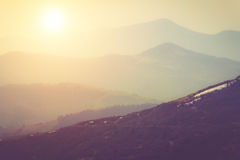 Layers of mountain and haze in the valleys. Fantastic evening glowing by sunlight. Stock Image
