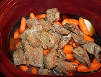 Layers of potatoes and carrots and browned stewing beef in a slow cooker with spices and added beef broth ready for cooking Royalty Free Stock Image