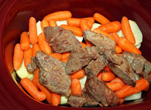 Layers of sliced white potatoes and carrots and browned stewing beef in a slow cooker Stock Photos