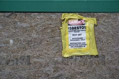 Danger Asbestos sign on particle board. Layers of yellow tape adhere the paper signage to the construction wall of wood shavings compressed flat.  Dangerous stock images
