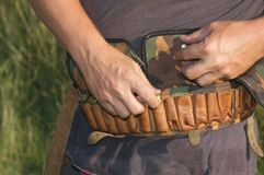 Laying of ammunition in a bandolier. Stacking ammo in a leather bandolier of hunter Royalty Free Stock Images