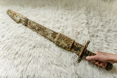 Laying the antique real sword on a handmade wool blanket stock photos