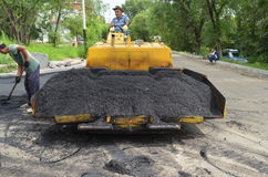 Laying of asphalt. The brigade of foreign workers, lay asphalt on the road Royalty Free Stock Photo